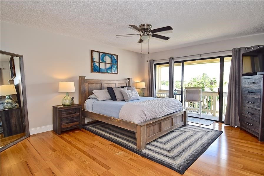large primary bedroom w/king bed & balcony